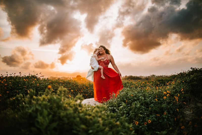 Atlanta Family Photographer, mom in red dress holds barefoot daughter as they walk through a flower field