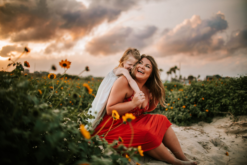 Atlanta Family Photographer, daughter hugs mom from behind in a flower field