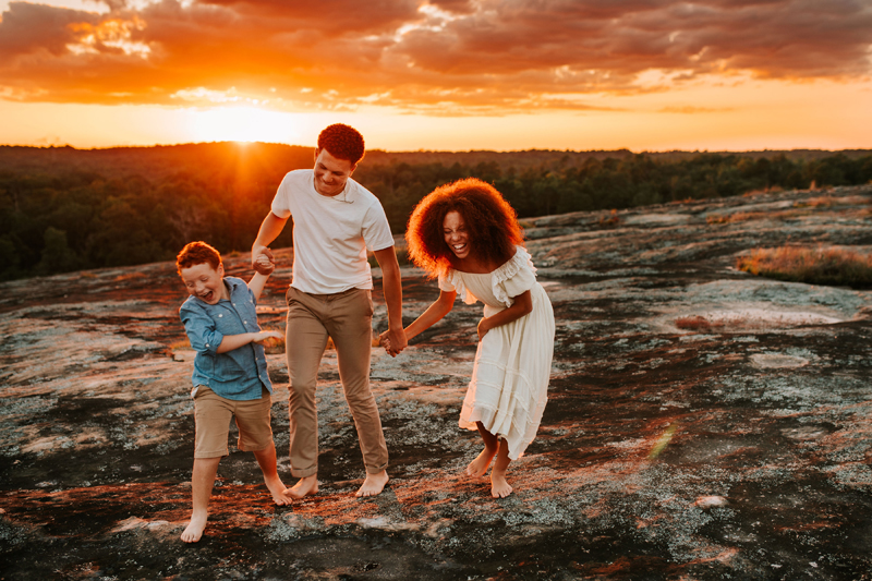 Atlanta Family Photographer, Dad, mom, and son all walk near the forest as sunset laughing