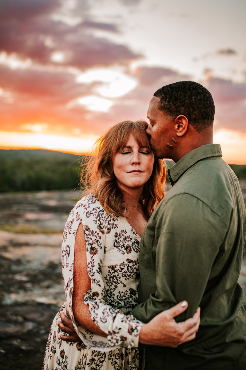 Atlanta Couples Photographer, man Kisses woman near forehead, they stand outside in nature