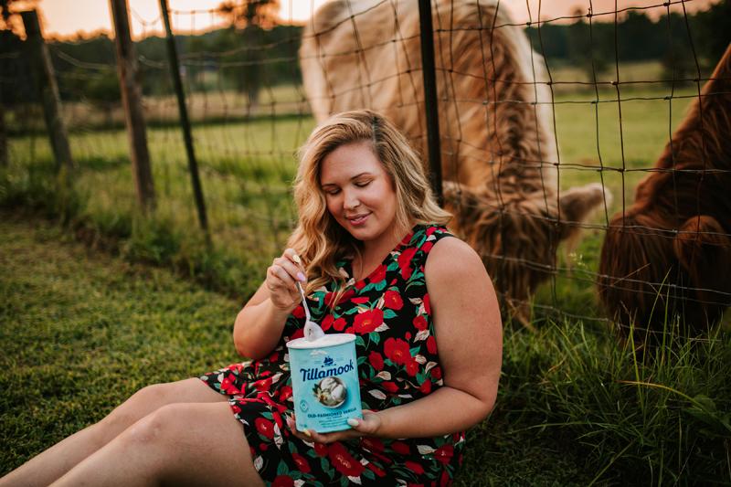 Atlanta Blogger-Influencer Photographer, a woman sits besides grazing farm animals as she eats tillamook ice cream