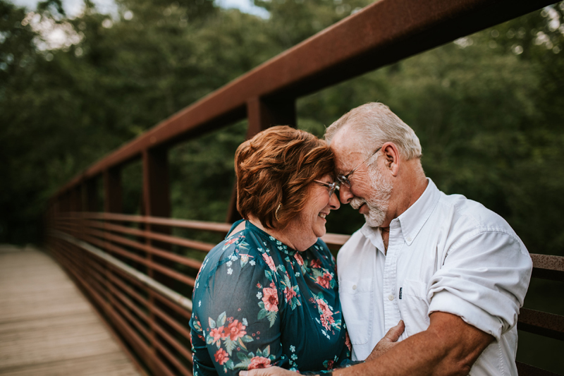 Atlanta Family Photographer, older couple embrace on a wooden bridge in the forest