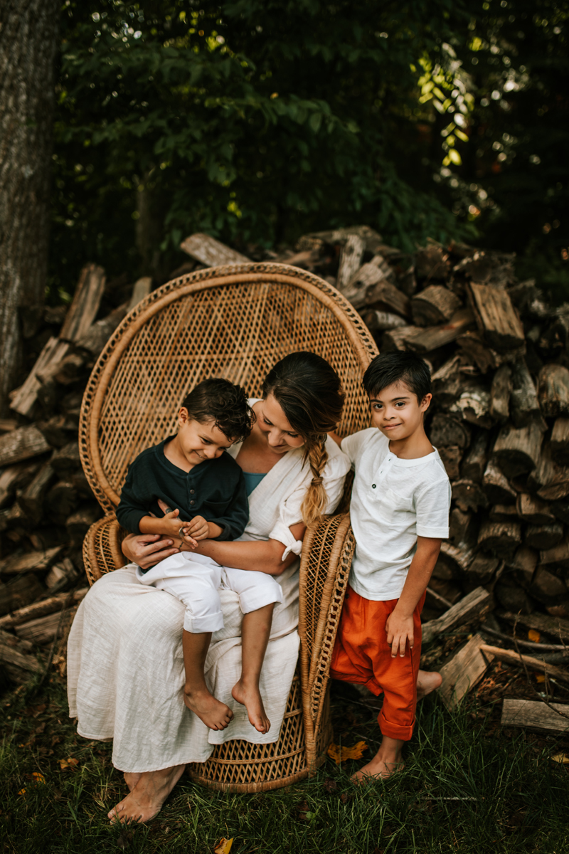 Atlanta Family Photographer, in big wicker chair, a mom sits with her two sons near large woodpile