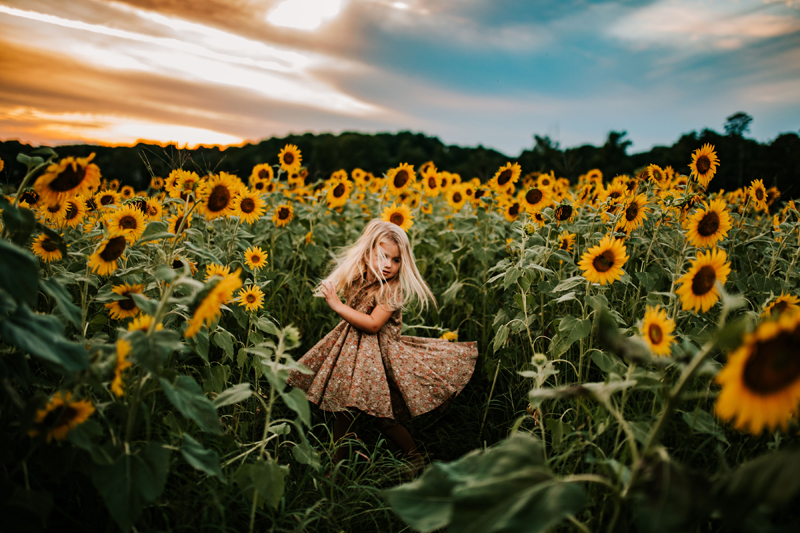 Atlanta Family Photographer, little girl spins in her dress surrounded by sunflowers