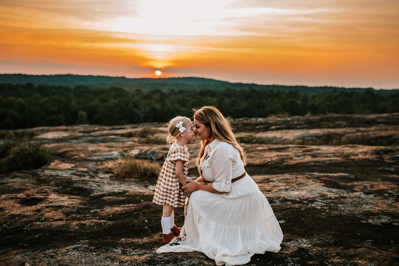 Atlanta Family Photographer, mom and daughter share eskimo kisses as they kneel before a backdrop of trees