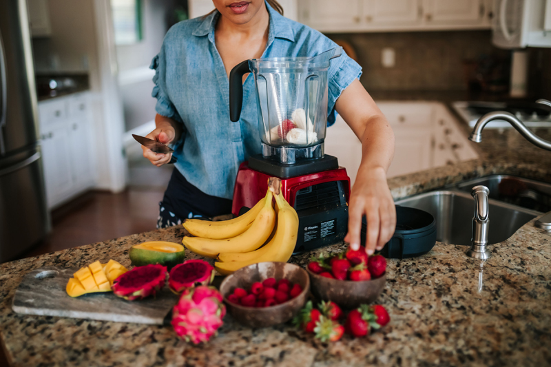 Atlanta Blogger-Influencer Photographer, Woman holds knife in kitchen to slice fruit before blending