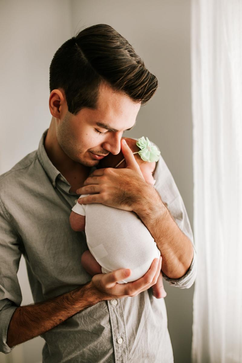 Atlanta Newborn Photographer, dad holds newborn daughter tightly