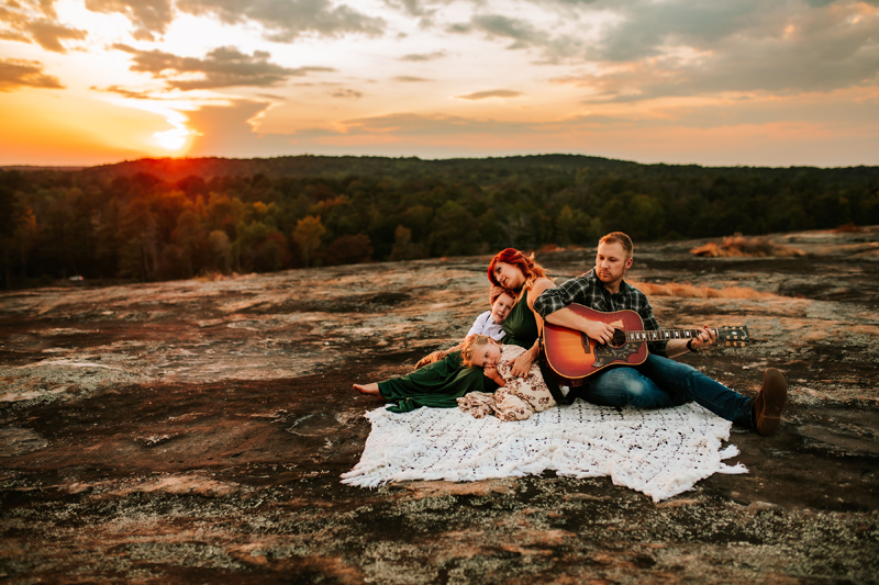 Atlanta Family Photographer, man plays the guitar for his wife and children on a blanket at sunset