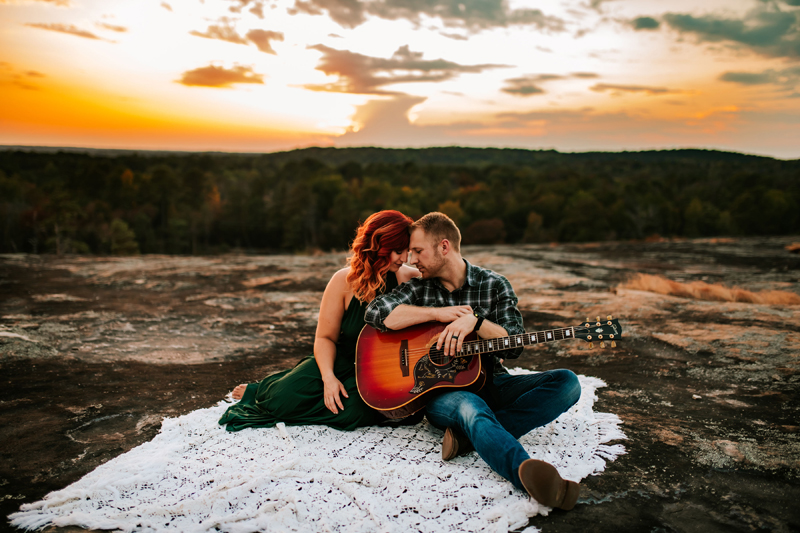 Atlanta Couples Photographer, a man and woman sit outdoors on a crocheted blanket, the man holding a guitar