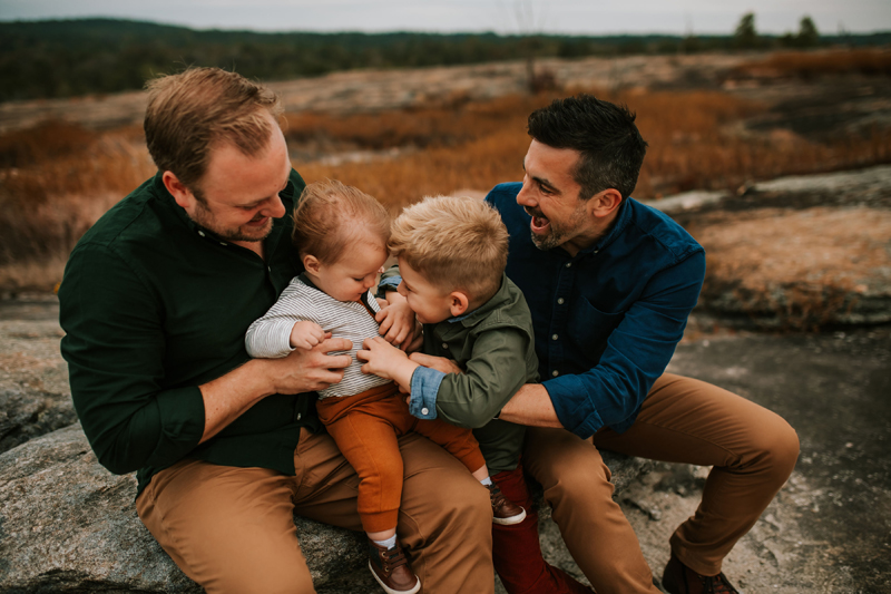 Atlanta Family Photographer, two dads hold their kids, all laughing joyfully