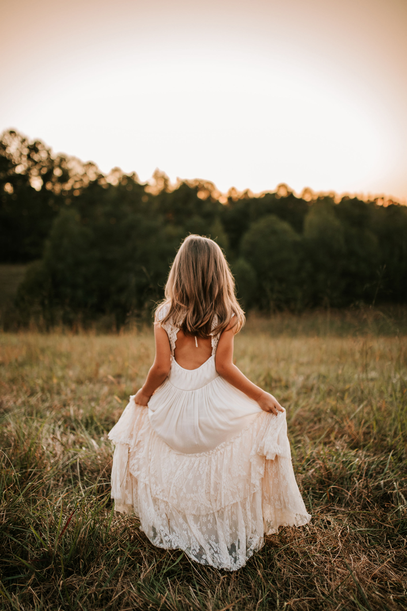Atlanta Family Photographer, woman in a dress walking toward the forest