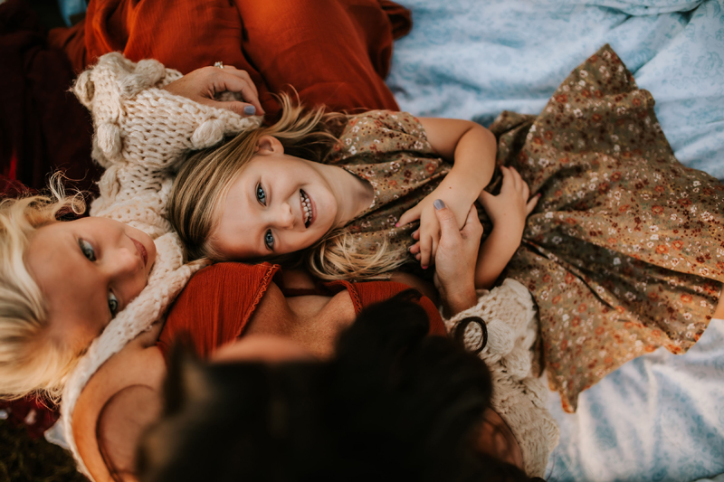 Atlanta Family Photographer, daughters lay in their mothers lap giggling and gazing at mom