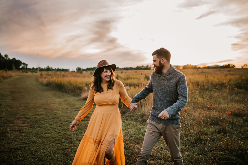 Atlanta Couples Photographer, man and woman lovingly hold hands walking through a field