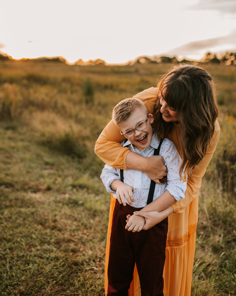 Atlanta Family Photographer, mom hugging son from behind in a grassy field