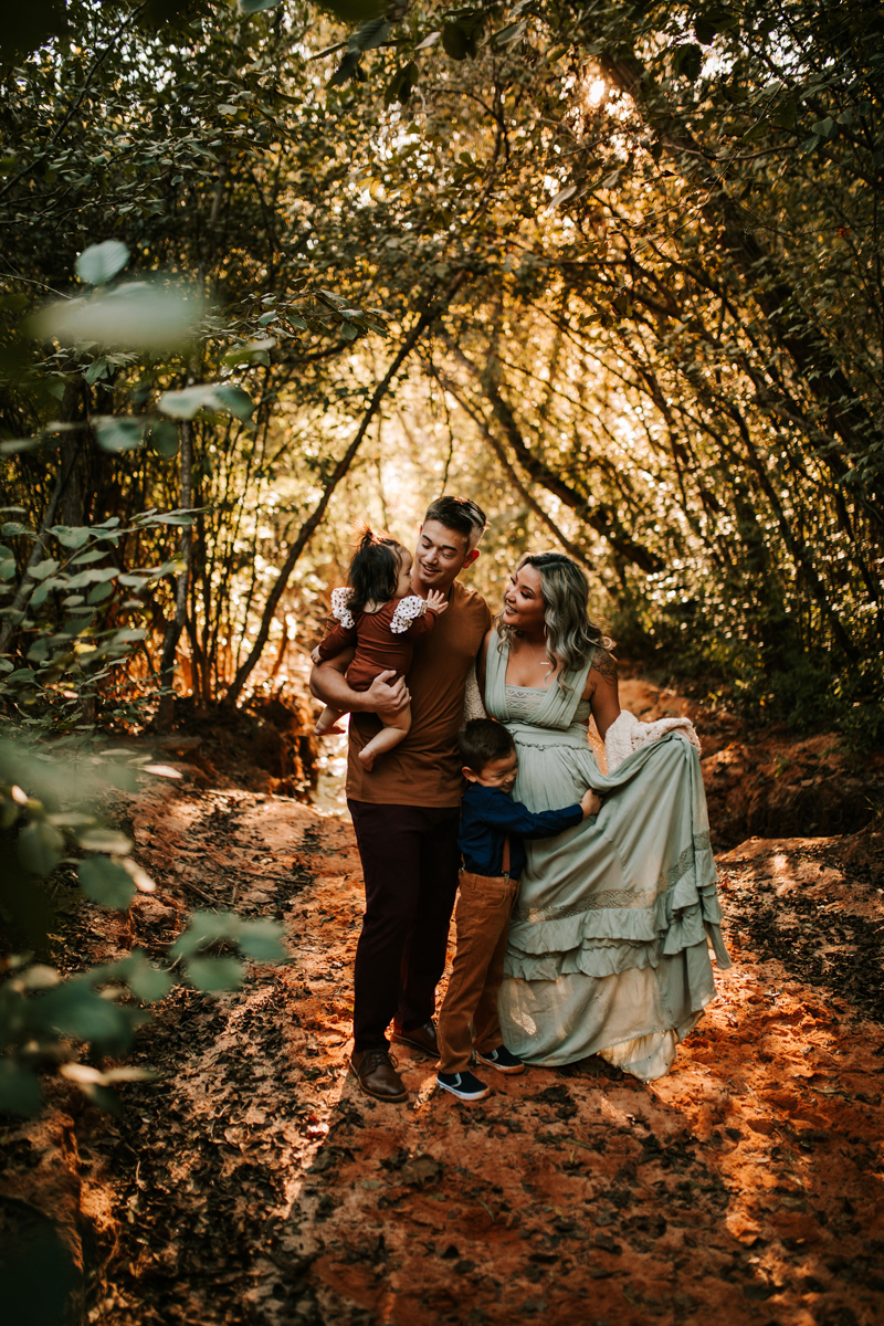 Atlanta Family Photographer, Mom, dad, son, and daughter stand happily within an enchanting forest