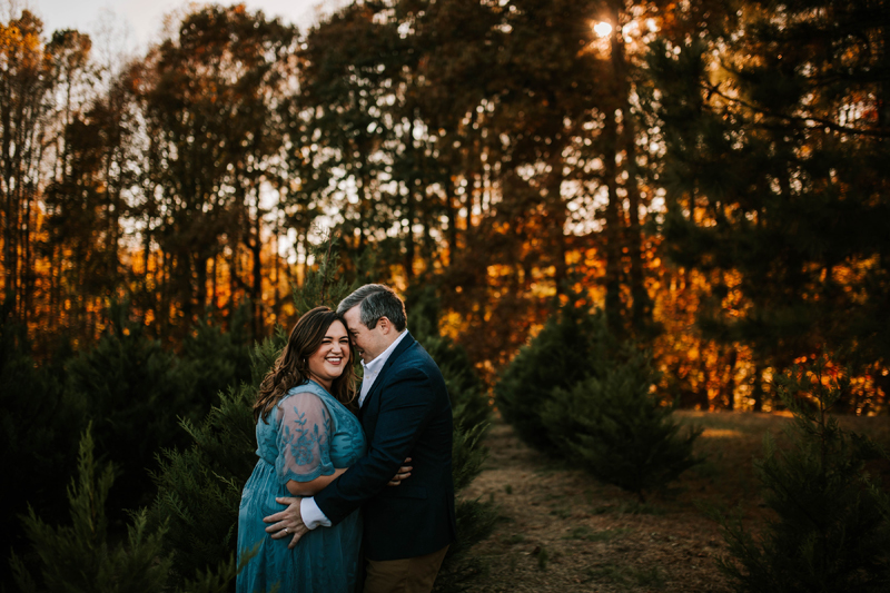 Atlanta Couples Photographer, husband holds wife near forest at sunset