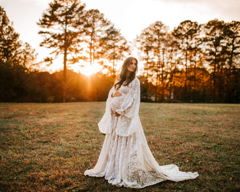 Atlanta Maternity Photographer, Pregnant mother stands near row of trees at sunset holding her belly