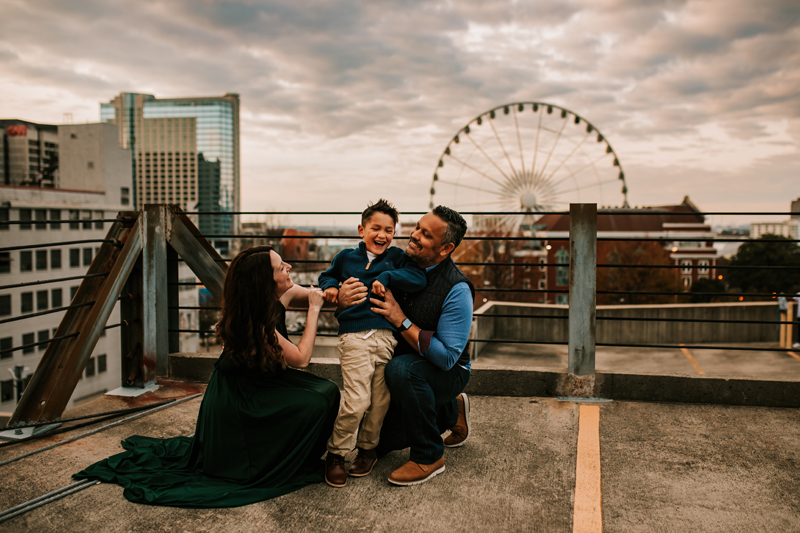 Atlanta Family Photographer, mom and dad admire son, all standing atop a city rooftop, ferris wheel behind them