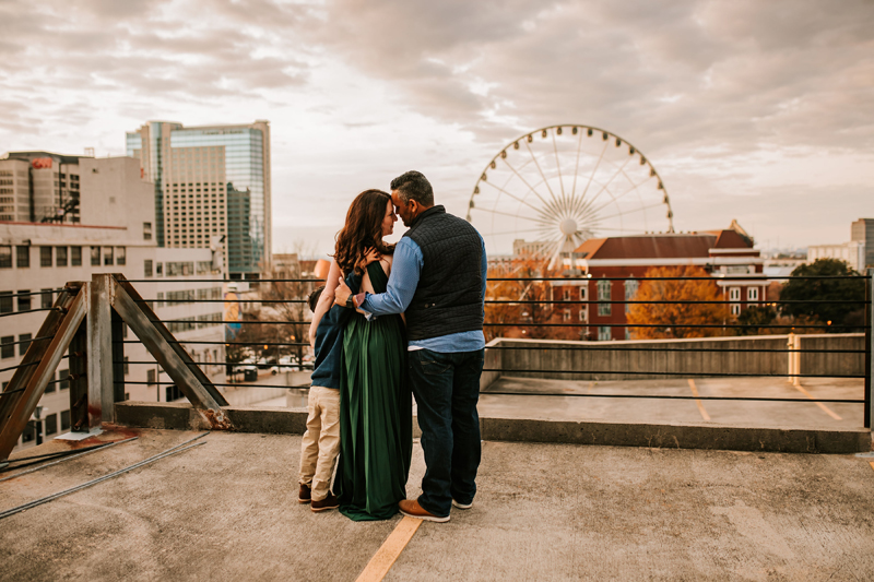 Atlanta Family Photographer, mom, dad and son admire urban cityscape from building rooftop