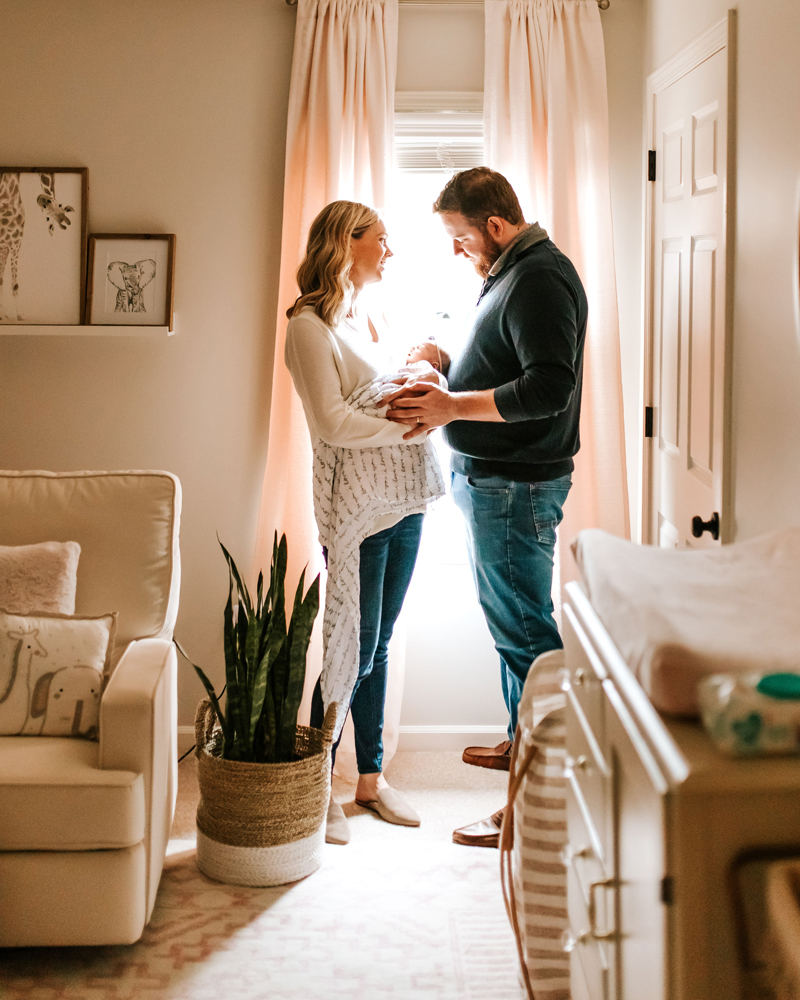 Atlanta Newborn Photographer, Dad and mom back at home with newborn in baby's beautifully decorated room