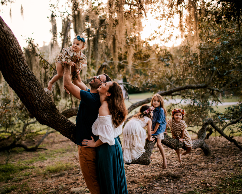 Atlanta Family Photographer, family with four girls, three of them climbing a tree, baby being admired by mom and dad