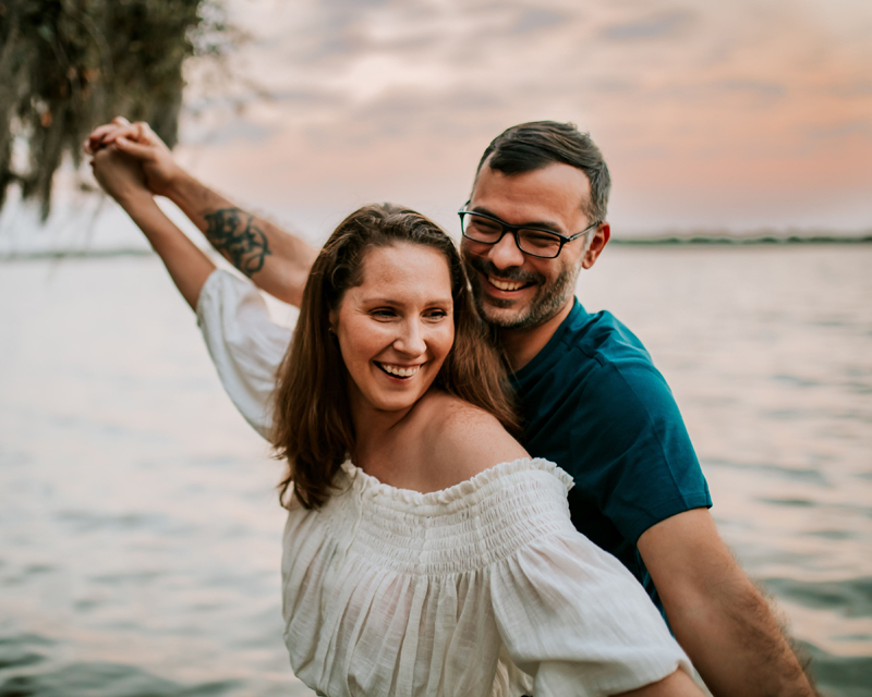 Atlanta Couples Photographer, man and woman laugh, playfully holding each other near lake front