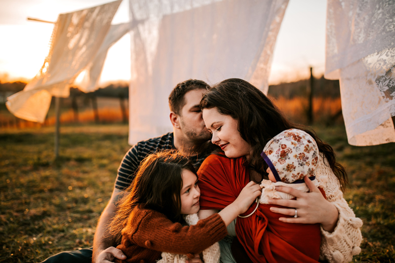 Atlanta Family Photographer, mom, dad, and daughter, with newborn baby in front of outdoor clothes line