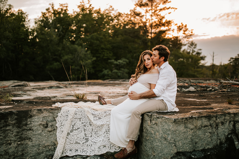 Atlanta Maternity Photographer, husband holds his expecting wife as they sit on the rocks near the trees