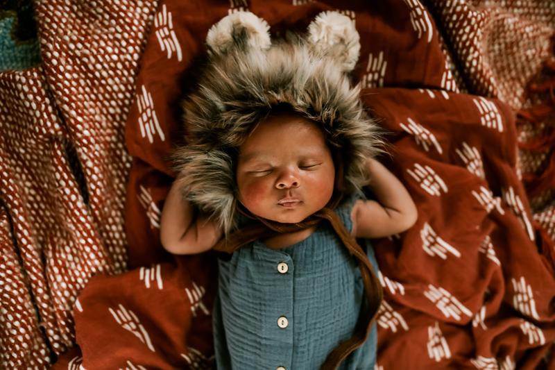 Atlanta Newborn Photographer, little baby wears fuzzy animal cap while laying blankets