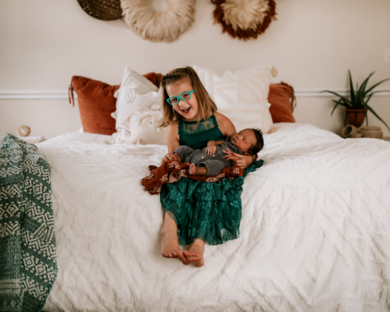 Atlanta Family Photographer, older sister olds newborn baby in her lap at home on parents bed