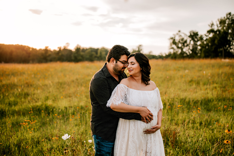 Atlanta Maternity Photographer, man fondly holds pregnant wife in grassy field