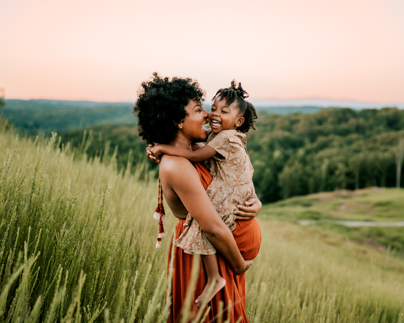 Atlanta Maternity Photographer, Pregnant mother holds young daughter in grassy field near the forest