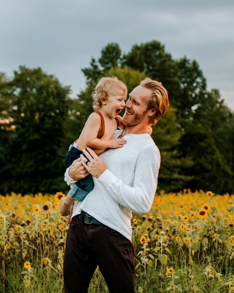 Atlanta Family Photographer, dad and toddler son laugh, walking through a field of sunflowers