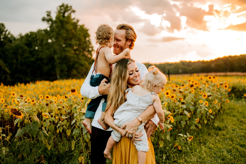 Atlanta Family Photographer, Happy parents hold their toddlers in front of a field of sunflowers