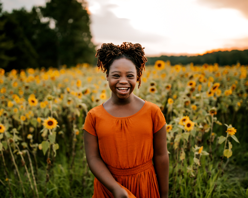 Atlanta Family Photographer, Girl has a big smile as she stands before a field of sunflowers