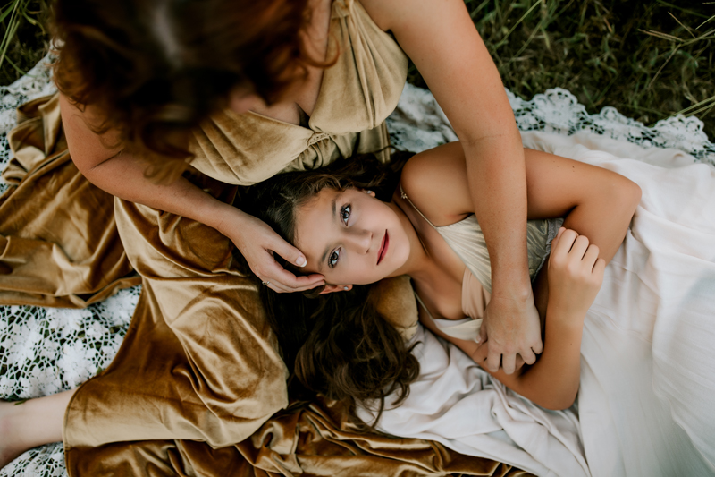 Atlanta Family Photographer, daughter lays in mothers lap dreamily looking up into the sky