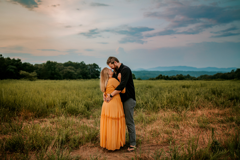 Atlanta Couples Photographer, couple embrace in field of grass at dusk