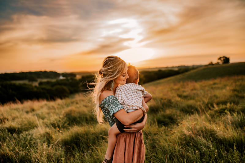 Atlanta Family Photographer, mother hugs toddler son on a windy hillside at sunset