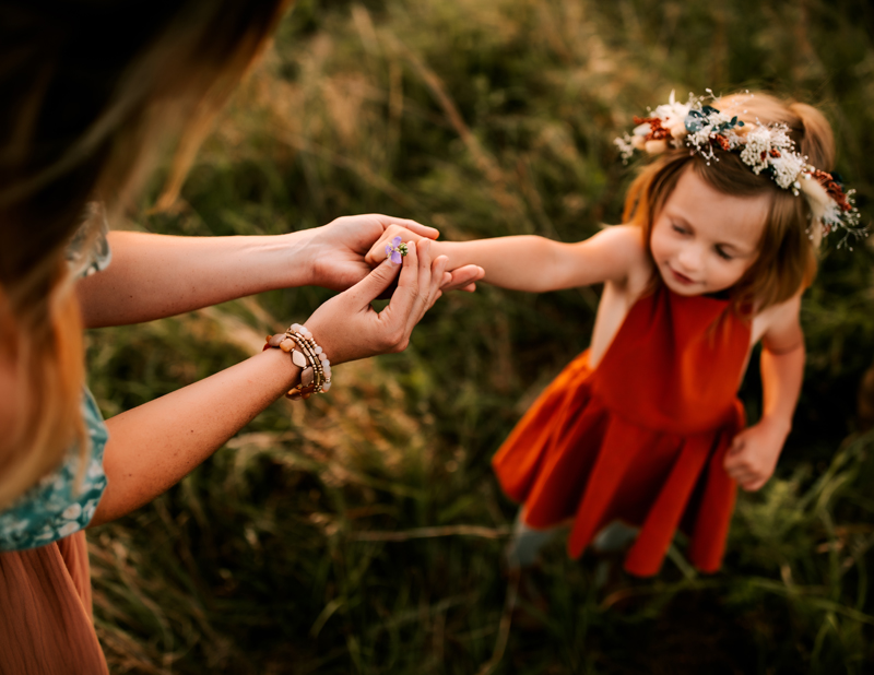 Atlanta Family Photographer, mom gives flower to little girl with a flower crown, her eyes tightly shut