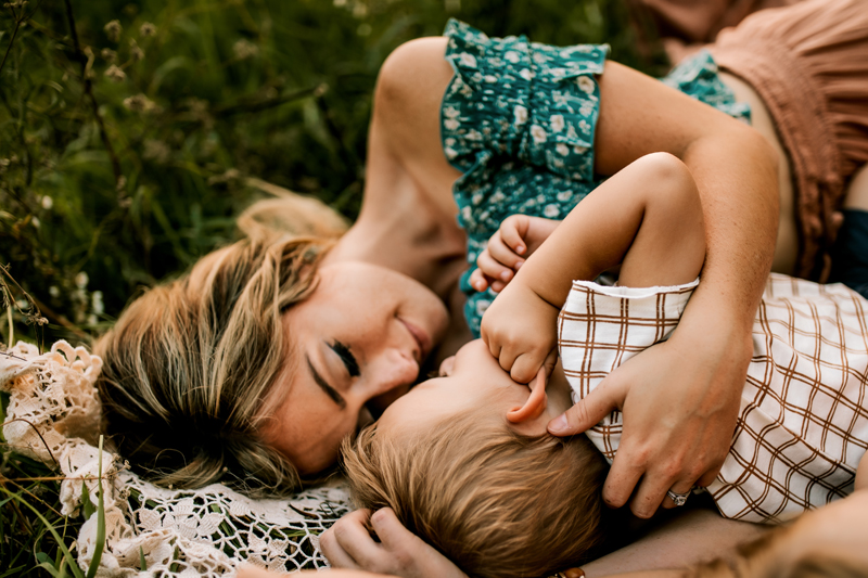 Atlanta Family Photographer, mother loves and dotes on toddler son as they lay on a blanket in the grass