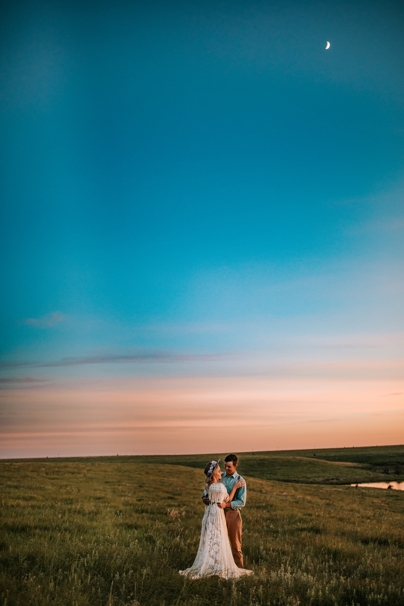 Atlanta Couples Photographer, couple hold each other in a field at dusk, the woman in her wedding dress