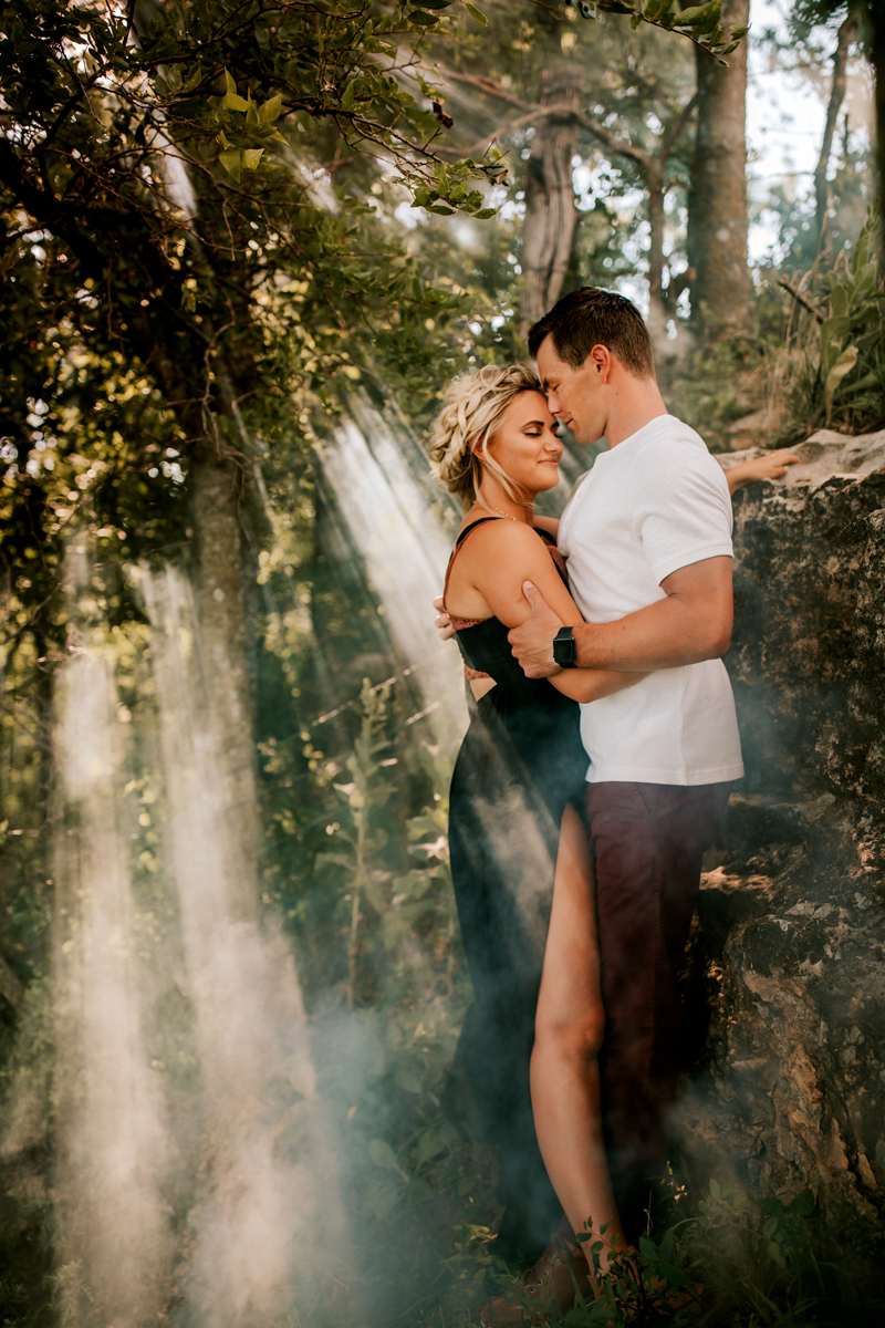 Atlanta Couples Photographer, light is beaming through a misty forest onto a couple holding themselves close.