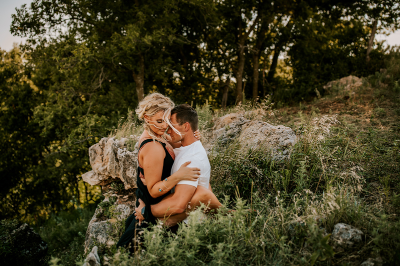 Atlanta Couples Photographer, man holds woman in steamy embrace outdoors near trees