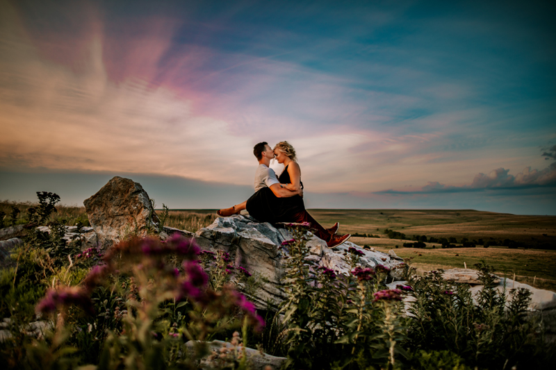 Atlanta Couples Photographer, a woman sits facing a man on his lap, they sit on on a rock within a field of flowers