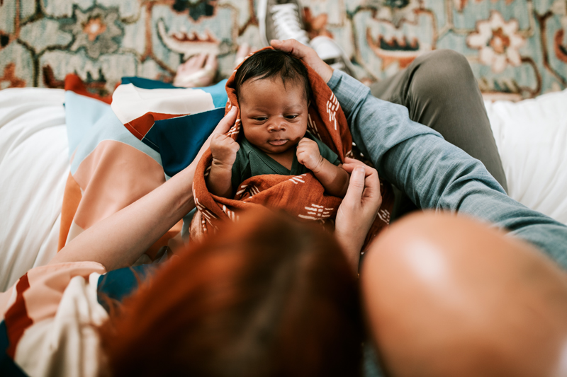 Atlanta Newborn Photographer, mom and dad have heads nudged together as they gaze down at their newborn baby