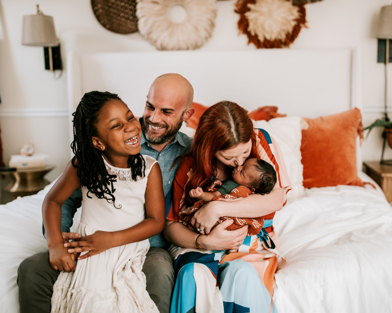 Atlanta Newborn Photographer, Family of four sit together laughing, mother kisses newborn baby