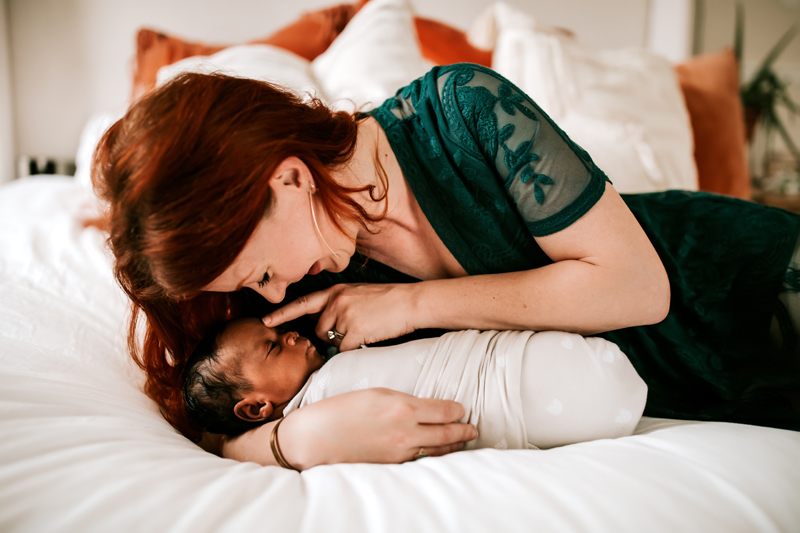 Atlanta Newborn Photographer, mother dotes on newborn as she holds baby closely on her bed