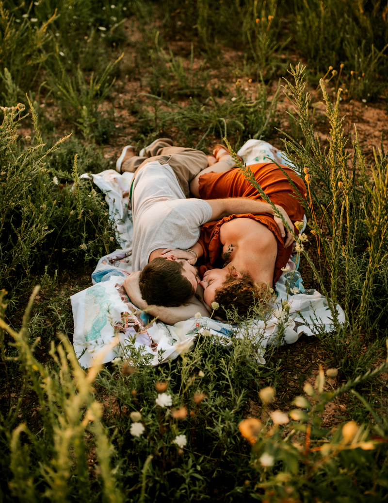 Atlanta Couples Photographer, man and woman lay on blanket together in field of flowers