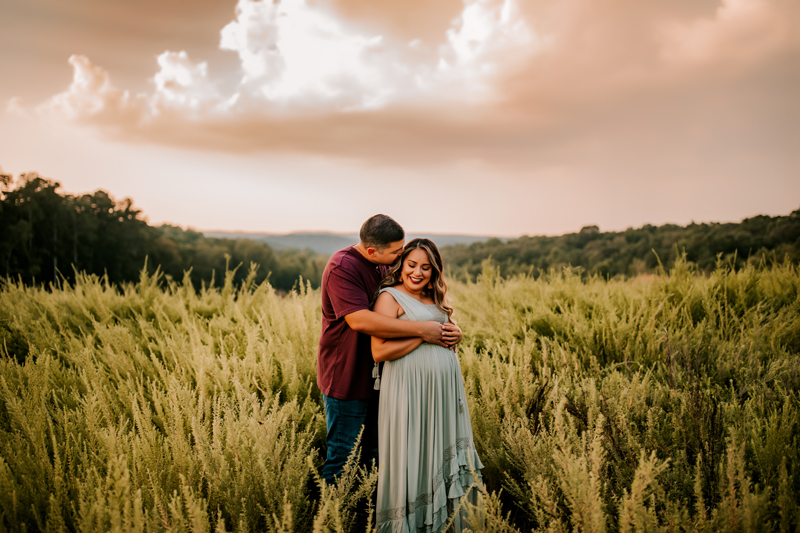Atlanta Maternity Photographer, Man embraces expectant woman, kissing her on head outdoors in field