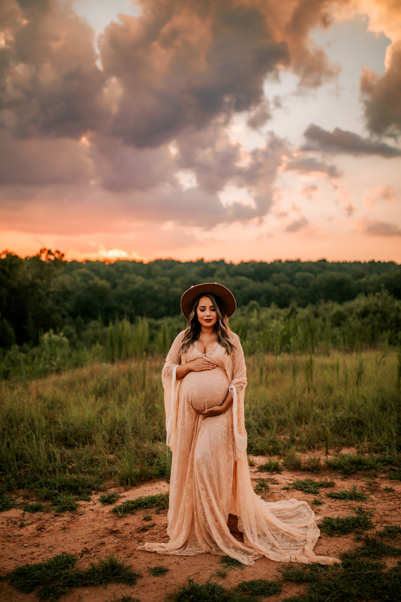 Atlanta Maternity Photographer, expectant mother holding belly thoughtfully near forest
